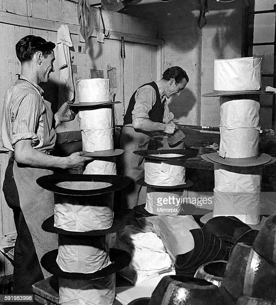 Here are Harry Parbott and Reg Marriott two top hat craftsmen pressing t hats they have made at Bermondsey London to export to Australia The hats are...