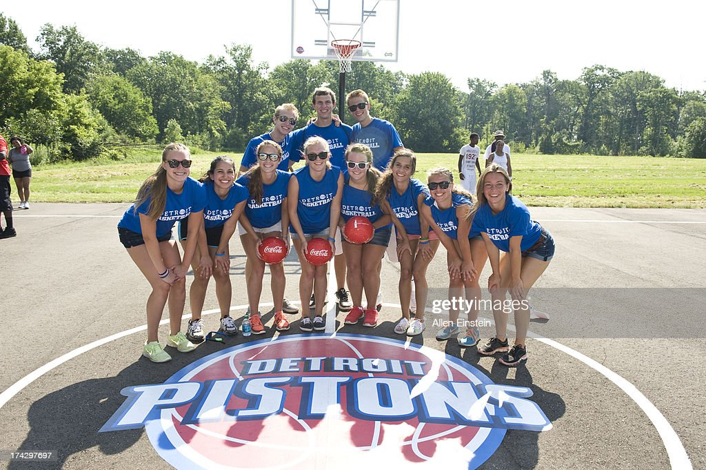 Here children pose for a photograph with the Detroit Pistons Logo on a local court Current Detroit Piston Andre Drummond and Pistons Legend Ric...