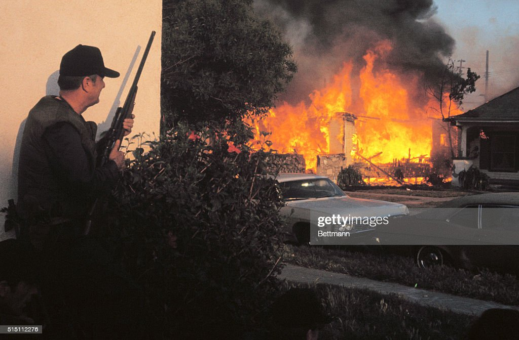 Here is one of the scenes from last night's shootout between police and Symbionese Liberation Army gunmen. A Los Angeles Police Officer hods a shotgun as he peers towards the burning house where members of the SLA, the group responsible for kidnapping newspaper heiress Patricia Hearst, were holed up.