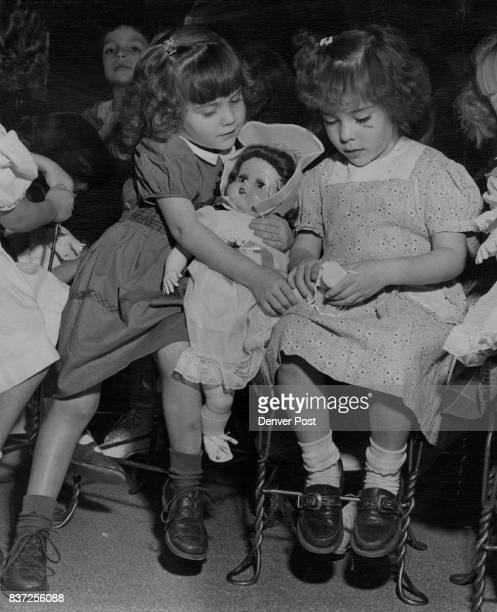 DEC 22 1950 'Here's the way her shoes go on' Theresa Maes explains as she ponders the intricacies of dressing her new doll with Doreen Bucci also 5...