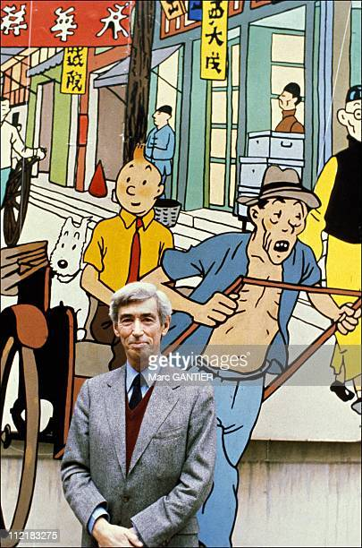 Herge poses for a portrait in front of a picture of his comic creation 'Tintin' in BrusselsBelgium