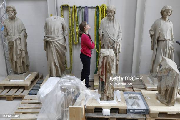 Heritage Curator of the Centre for Research and Restoration of Museums of France Alexandra Gerard examines polychrome stone statues belonging to the...