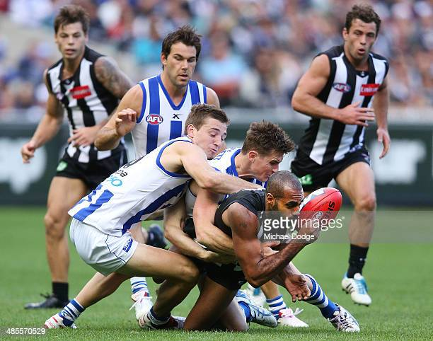 Heritier Lumumba of the Magpies is tackled by Shaun Atley and Aaron Mullett of the Kangaroos during the round five AFL match between the Collingwood...