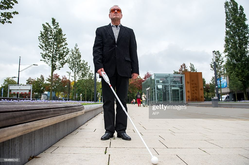 Herman Evers of the Dutch company I-cane demonstrates on October 15, 2013 in the eastern Dutch city of Nijmegen the I-Cane Mobilo, which includes navigation and sensor technology that can be connected to a smartphone and help navigate visually impaired people past obstacles. Users can record personal routes to repeat these independently later. AFP PHOTO / ANP / FERDY DAMMAN - netherlands out -