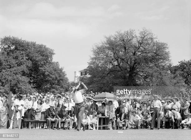 Herman Keiser tees off on the first tee as Byron Nelson and a large gallery watch during a 1946 Masters Tournament at Augusta National Golf Club in...