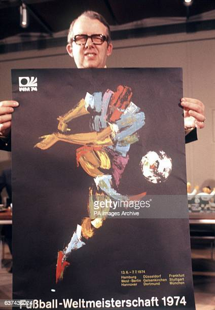 Hermann Neuberger President of the FIFA Organising Committee holds up the official poster of the 1974 World Cup Finals