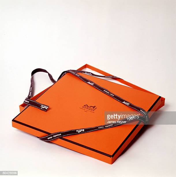 Hermes gift box in orange w embossed co logo tied w brown ribbon w repeated white logo