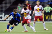 Hernan Bernardello of the Montreal Impact runs with the ball in front of Peguy Luyindula of the New York RedBulls during the MLS game at the Olympic...