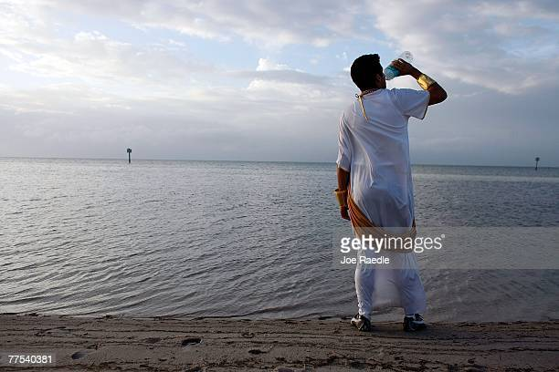 Hernan Castillo who said he was dressed as Julius Caesar greets the morning with a drink of water next to the ocean during Fantasy Fest October 28...