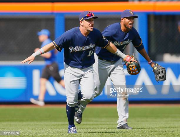 Hernan Perez and Domingo Santana of the Milwaukee Brewers run in from the outfield with arms outstretched like a jet plane celebrating after an MLB...