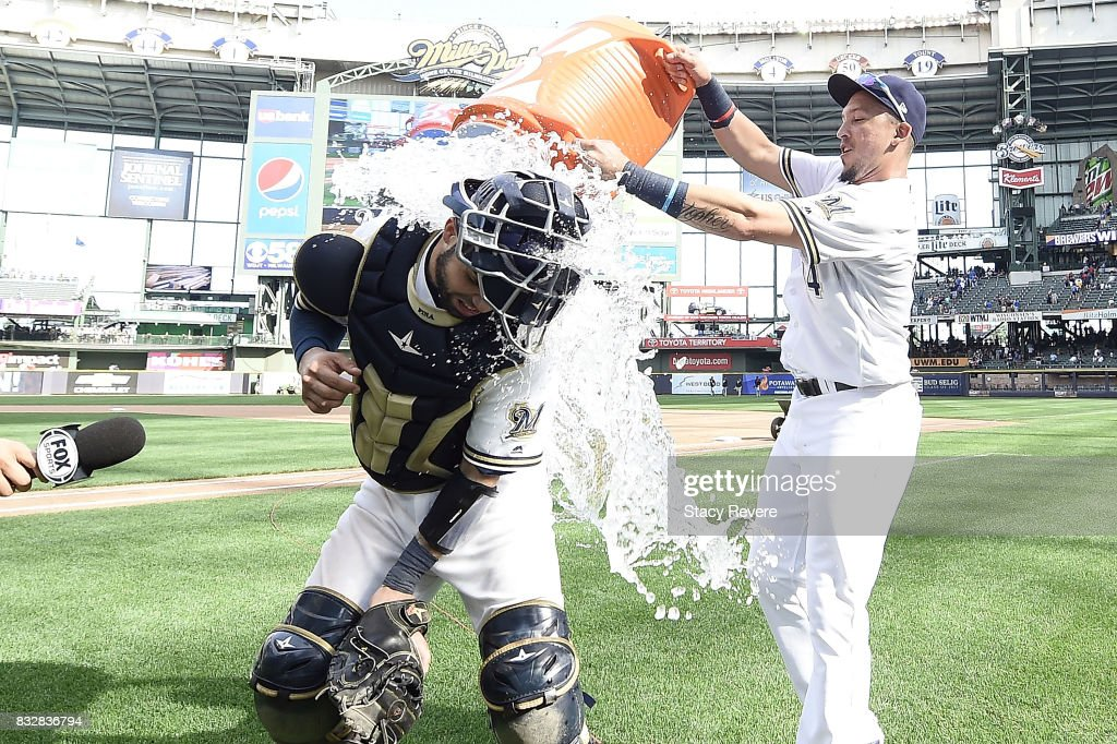 Hernan Perez #14 of the Milwaukee Brewers dunks Manny Pina #9 following a victory over the Pittsburgh Pirates at Miller Park on August 16, 2017 in Milwaukee, Wisconsin. The Brewers defeated the Piratrers 7-6.
