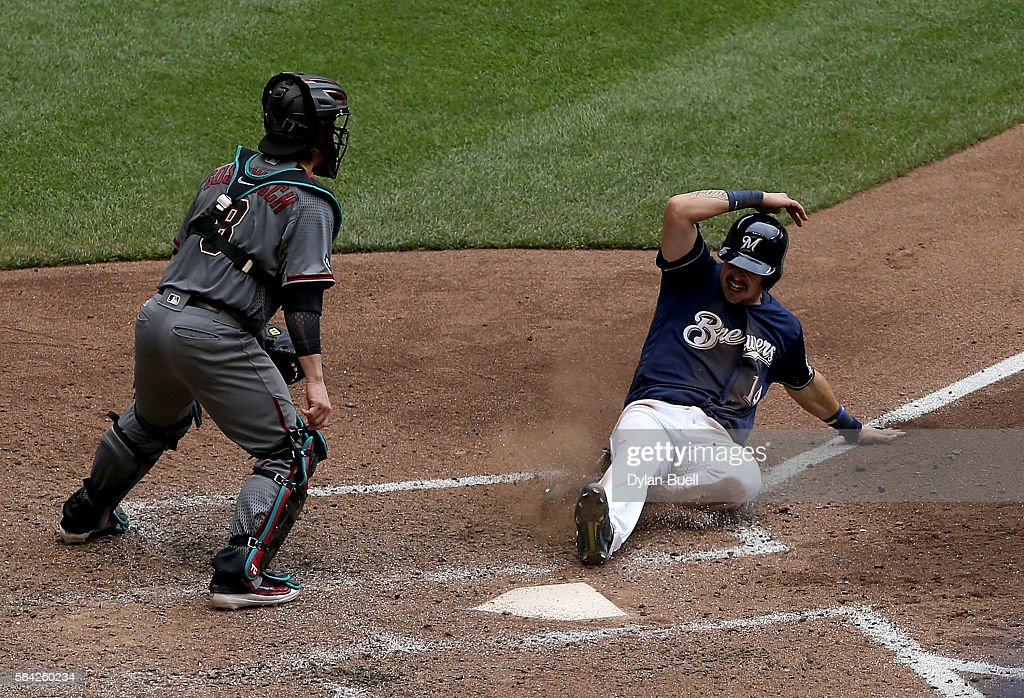 Hernan Perez of the Milwaukee Brewers slides into home to score a run past Tuffy Gosewisch of the Arizona Diamondbacks in the sixth inning at Miller...