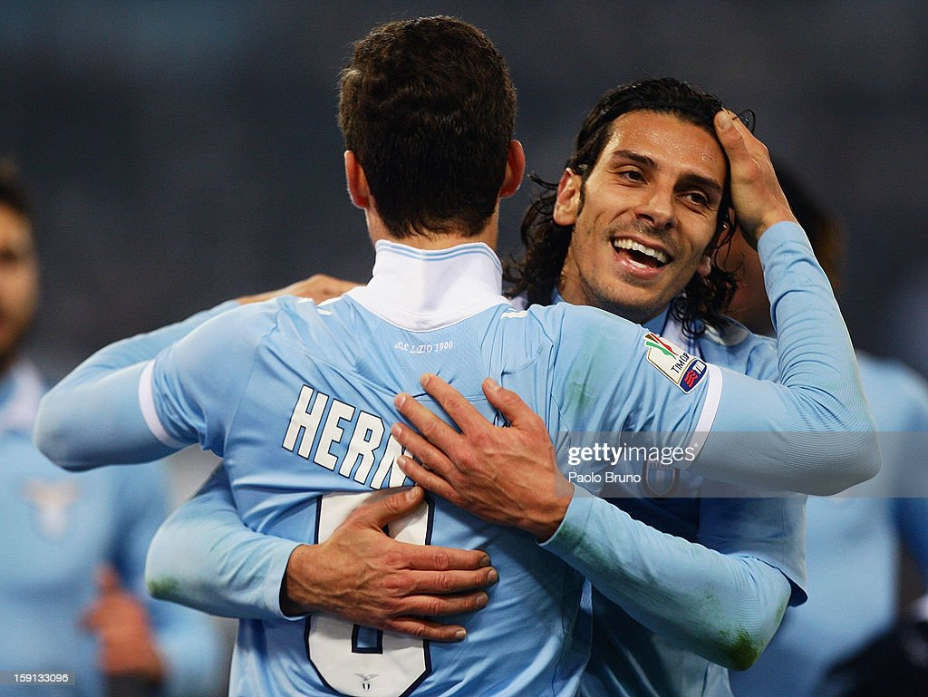 <a gi-track='captionPersonalityLinkClicked' href=/galleries/search?phrase=Hernanes&family=editorial&specificpeople=4522139 ng-click='$event.stopPropagation()'>Hernanes</a> (L) is congratulated by SS Lazio team-mate <a gi-track='captionPersonalityLinkClicked' href=/galleries/search?phrase=Sergio+Floccari&family=editorial&specificpeople=675401 ng-click='$event.stopPropagation()'>Sergio Floccari</a> after scoring their team's second goal during the TIM Cup match between S.S. Lazio and Calcio Catania at Stadio Olimpico on January 8, 2013 in Rome, Italy.