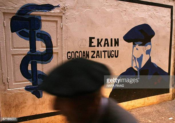 A man walks past a mural painting representing the proindependence armed Basque group ETA logo and honouring an activist who died when the bomb that...
