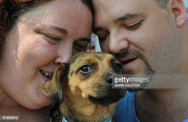 Hero Dog 'Miley' is cuddled by owners Stacie Pitts and Randy Childers after receiving the 27th Annual National Hero Dog Award for saving them from...