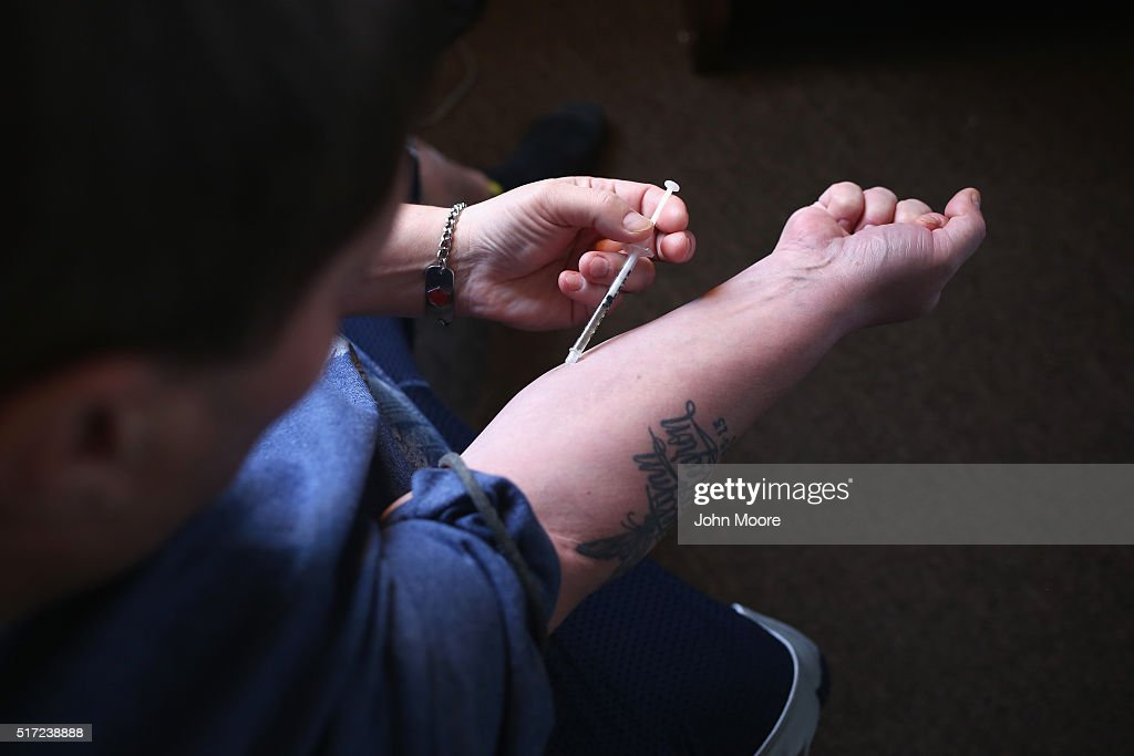 A heroin user injects himself on March 23 2016 in New London CT Communities nationwide are struggling with the unprecidented heroin and opioid pain...