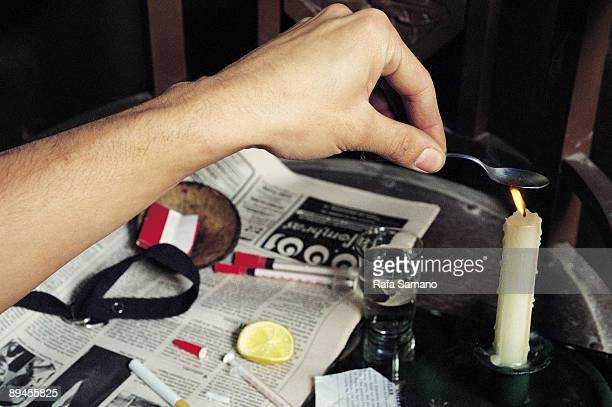 Heroin user preparing his fix Heroin addict heats the drug next to the necessary material to prepare his fix