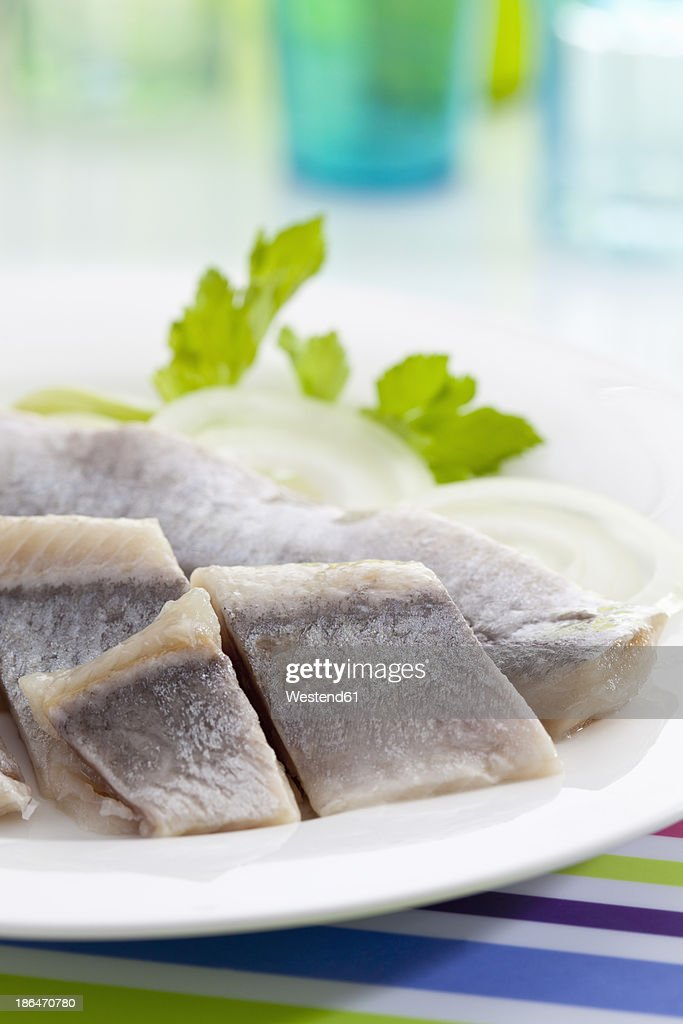 Herring in oil with onions on plate, close up