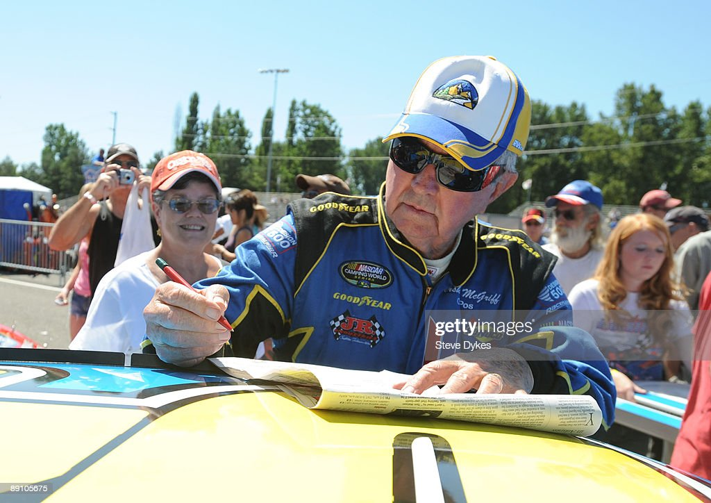 Hershel McGriff is surrounded by fans as he signs autographs in the pit area before qualifying for the NASCAR Camping World Series West BI-MART Salute to the Troops 125 at Portland International Raceway on July 19, 2009 in Portland, Oregon.