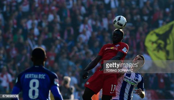 Hertha Berlins Bosnian forward Vedad Ibisevic and Leipzig's Oswald Upamecano head for the ball during the German First division Bundesliga football...