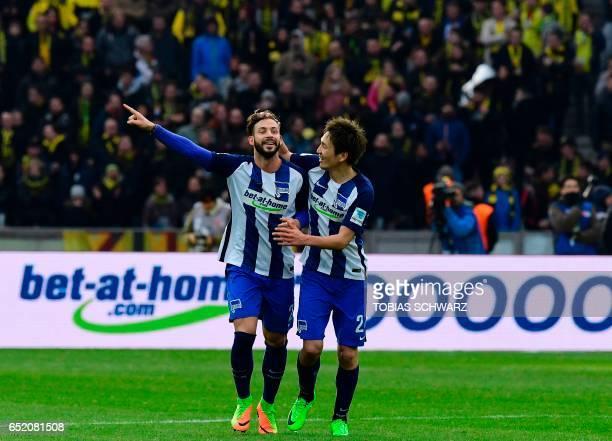 Hertha Berlin's defender Marvin Plattenhardt is congratulated by Hertha Berlin's Japanese midfielder Genki Haraguchi after scoring the 21 during the...