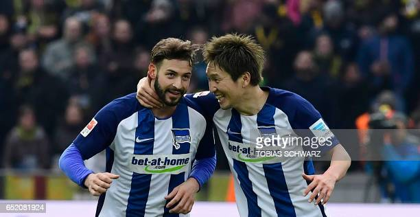 Hertha Berlin's defender Marvin Plattenhardt is congratulated by Hertha Berlin's Japanese midfielder Genki Haraguchi after scoring the 21 during the...
