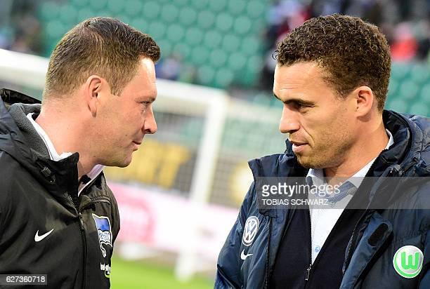 Hertha Berlin's Hungarian head coach Pal Dardai and Wolfsburg head coach Valerien Ismael chat before the German first division Bundesliga football...