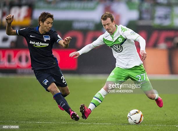Hertha Berlin's Japanese forward Genki Haraguchi and Wolfsburg's midfielder Maximilian Arnold vie for the ball during the German first division...