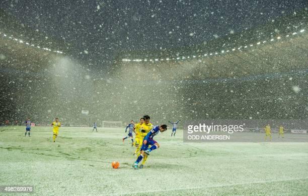 Hertha Berlin's Japanese midfielder Genki Haraguchi and Hoffenheim's Korean defender JinSu Kim vie for the ball in heavy snow during the German first...