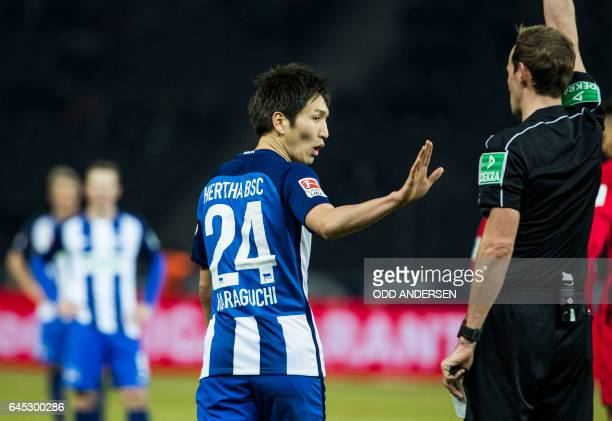 Hertha Berlin's Japanese midfielder Genki Haraguchi remonstrates with referee Sascha Stegemann giving him a yellow card during the German first...