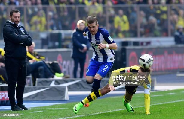 Hertha Berlin's Slovakian defender Peter Pekarik and Dortmund's Marcel Schmelzer as Berlin's Hungarian head coach Pal Dardai watches during the...
