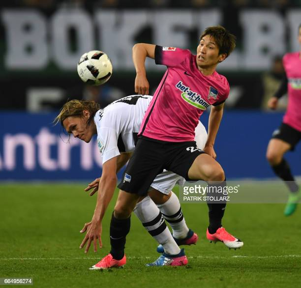 Hertha's Japanese midfielder Genki Haraguchi and Moenchengladbach's Danish defender Jannik Vestergaard vie for the ball during the German first...