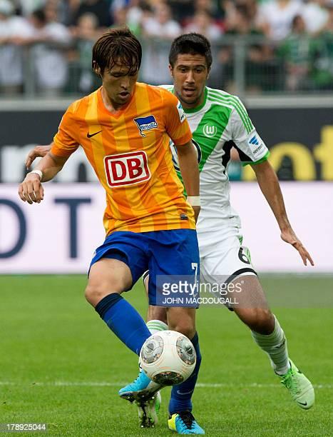 Hertha's Japanese midfielder Hajime Hosogai and Wolfsburg's Serbian midfielder Slobodan Medojevic for the ball during the German first division...