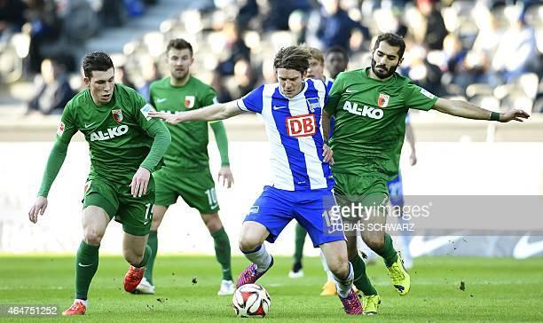 Hertha's midfielder Peter Niemeyer Augsburg's Danish midfielder Pierre Emile Hoejbjerg and Augsburg's Turkish midfielder Halil Altintop vie for the...