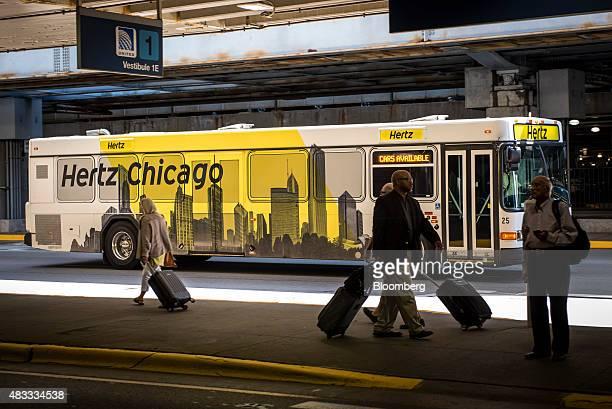 A Hertz Global Holdings Inc shuttle bus drives past travelers at O'Hare International Airport in Chicago Illinois US on Thursday Aug 6 2015 Hertz is...