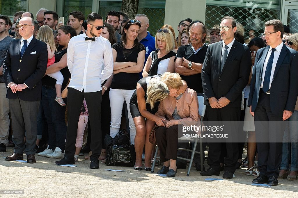 Herve Cornara's wife Laurence comforts the mother Lucette, as French Interior Minister Bernard Cazeneuve (L), Herve Cornara's son Kevin (2nd L) and brother Didier Cornara (2nd R), attend a memorial ceremony on June 26, 2016 in Fontaines-sur-Saone, in tribute to Herve Cornara, killed one year ago in a terror attack at the Air Products factory in Saint-Quentin-Fallavier. In June, 2015, Yassin Salhi beheaded Herve Cornara, owner of a company where he had worked near Lyon. / AFP / ROMAIN