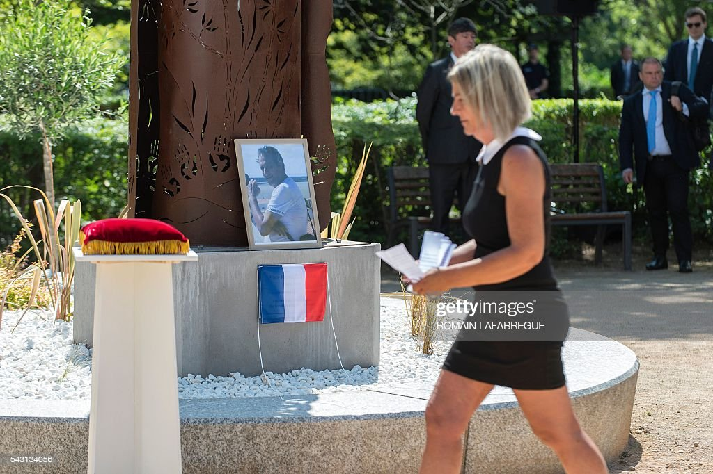 Herve Cornara's wife Laurence walks past a portrait to his husband during a memorial ceremony on June 26, 2016 in Fontaines-sur-Saone, in tribute to Herve Cornara, killed one year ago in a terror attack at the Air Products factory in Saint-Quentin-Fallavier. In June, 2015, Yassin Salhi beheaded Herve Cornara, owner of a company where he had worked near Lyon. / AFP / ROMAIN