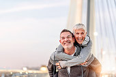 Photo of Happy mature couple having fun, hugging in the city on a autumn day. Love story true feelings concept. Portrait of friendly peaceful fitness couple in love. Couple enjoying the outdoors toget