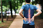 Rear view shot of a sporty young man holding his back in pain while exercising outdoors