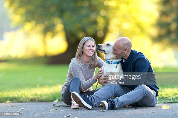 Heterosexual couple and their dog enjoying an evening outside