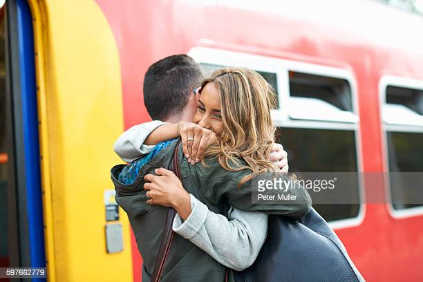 Heterosexual couple hugging at railway station