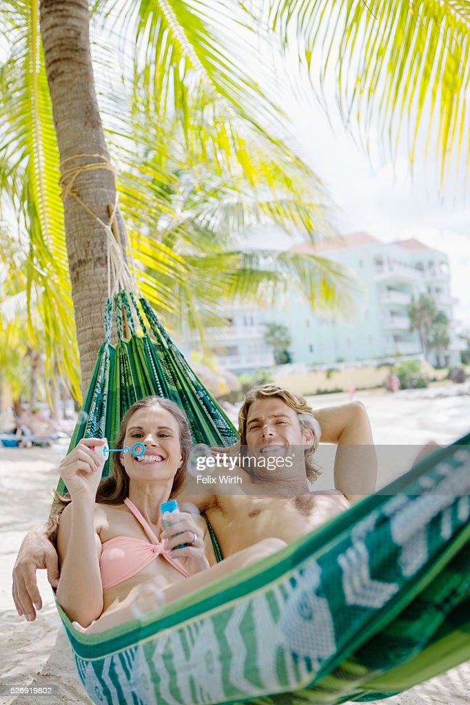 Heterosexual couple relaxing in hammock on beach blowing soap bubbles : ストックフォト