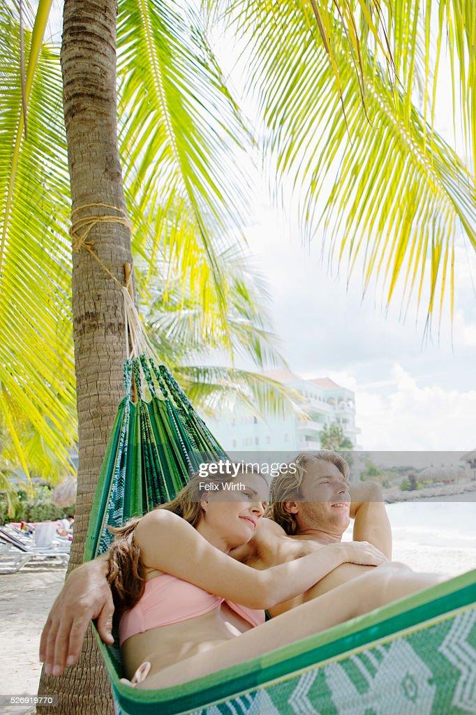 Heterosexual couple relaxing in hammock on beach : Bildbanksbilder