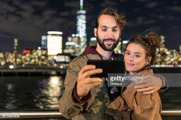 Heterosexual Couple Taking Selfie Pictures With Mobile Phone with NYC in the Background