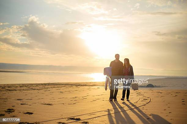 Heterosexual couple walking at sunset at the beach