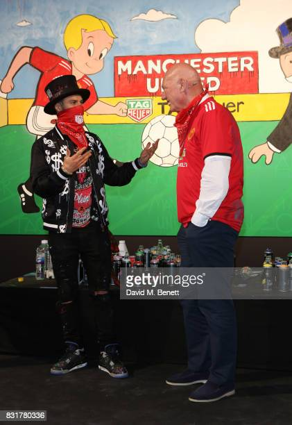 TAG Heuer Art Provocateur Alec Monopoly and TAG Heuer CEO and President of LVMH Watch Division JeanClaude Biver unveil new artwork at Old Trafford on...