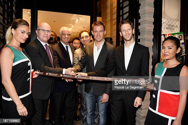 TAG Heuer's CEO Stephane Linder Antonio Belloni Sebastien Ogier and Romain Grosjean cut the ribbon at the Opening of the TAG Heuer New Boutique...