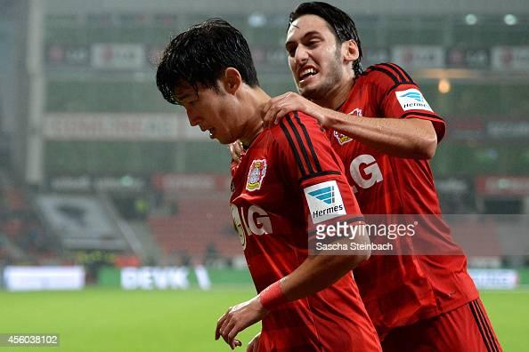 Heung Min Son of Leverkusen celebrates with team mate Hakan Calhanoglu after scoring the opening goal during the Bundesliga match between Bayer 04...