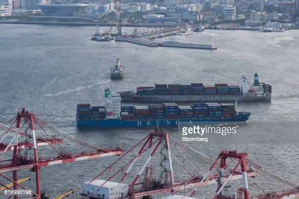 A HeungA Shipping Co container ship and a Wan Hai Lines Ltd container ship travel past the Busan Port Terminal in Busan South Koreaon Sunday July 16...
