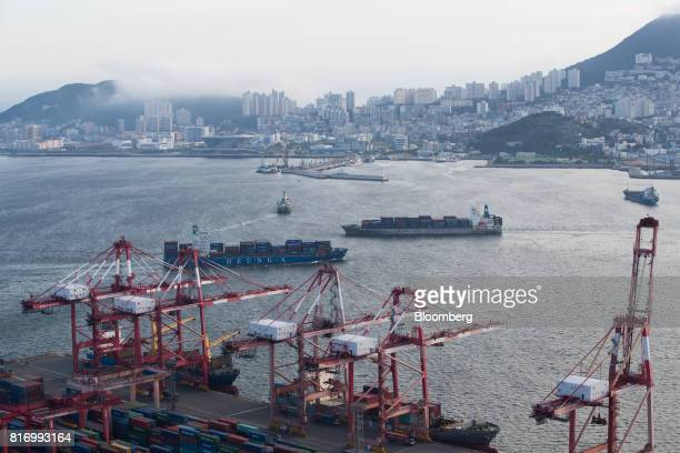 A HeungA Shipping Co container ship left and a Wan Hai Lines Ltd container ship sail past the Busan Port Terminal in Busan South Koreaon Sunday July...